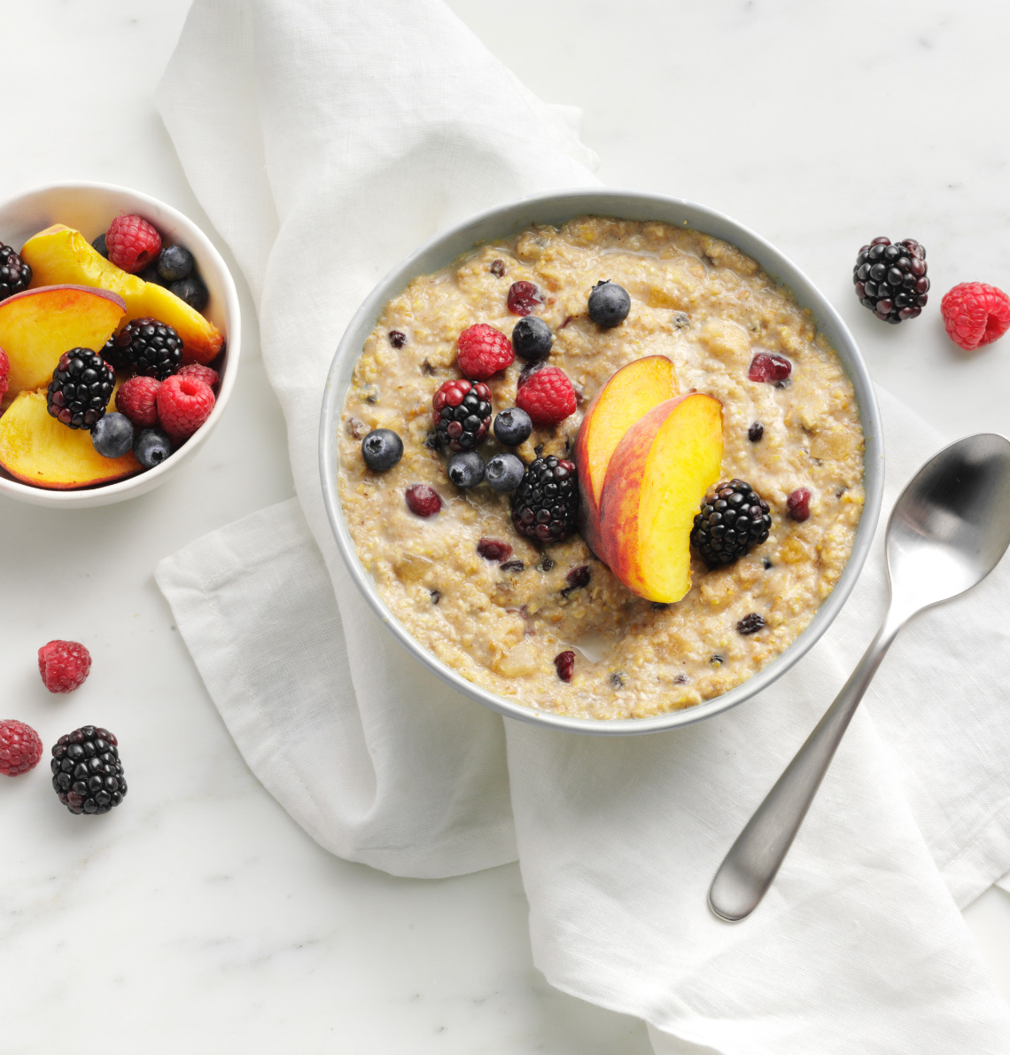 Bowl of HMR hot cereal prepared with fresh berries and sliced fruit